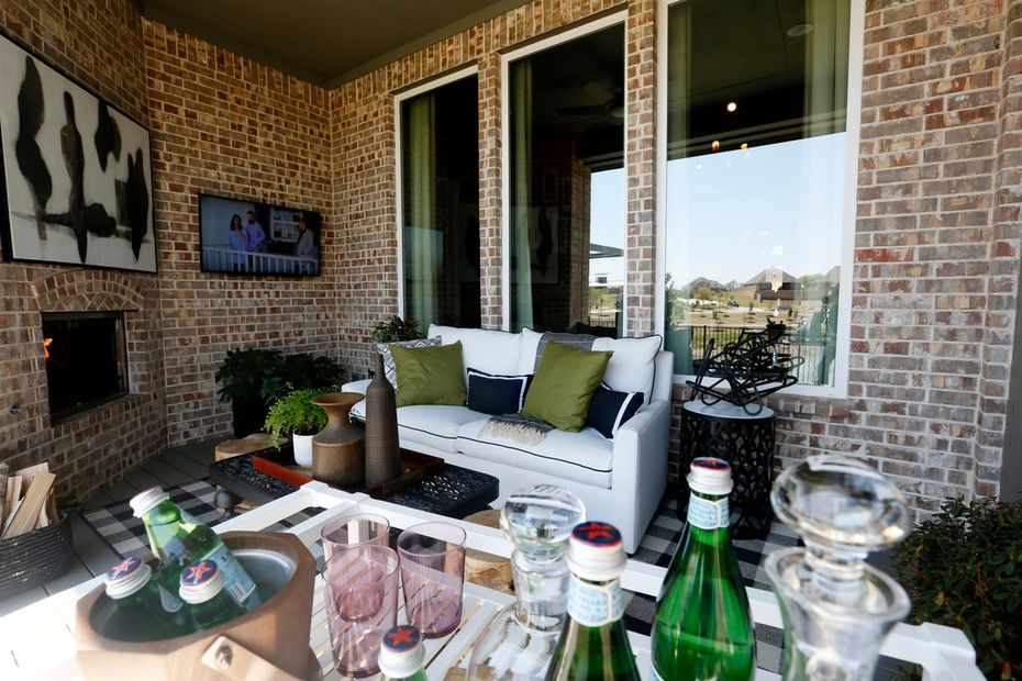 HGTV's Smart Home in Roanoke has a covered patio. The backyard extends around the house, with another sitting area with an outdoor movie screen.