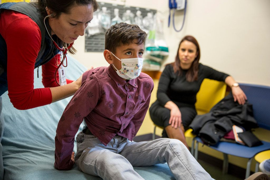 A doctor examines Christopher Serrano, 10, who is covered by the Children's Health Insurance Program, at Dell Children's Medical Center in Austin Jan. 7, 2018. With no immigration deal in sight, Republicans are eyeing a stopgap bill to keep the government open past Friday, sweetening it with an extension of the child health program. (Ilana Panich-Linsman/The New York Times)