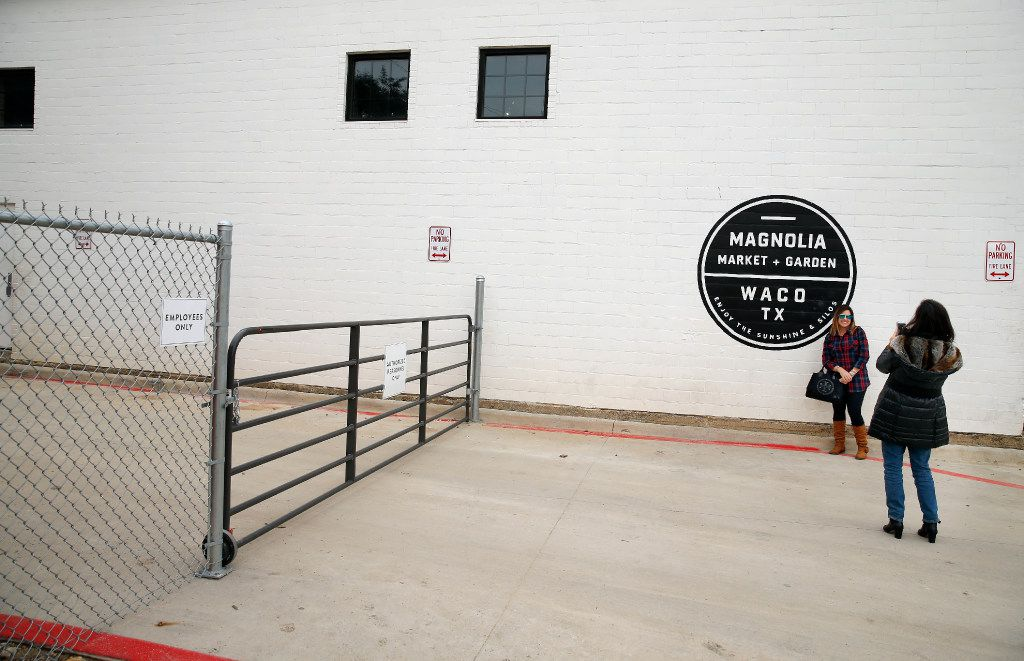 Shoppers take photos near the gate crossing a driveway on the south end of Chip and Joanna Gaines' Magnolia Market in Waco, Texas, Wednesday, December 7, 2016. (Tom Fox/The Dallas Morning News)
