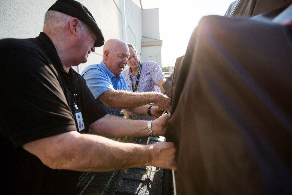 From left, Department of Family and Protective Services special investigators Don Frisch (cq), Jeff Landrum and John Vandervalk (cq) tie down a tarp on one of the trucks as they prepare to restock the Rainbow Room in Houston with things like infant formula, cleaning supplies, hygiene items, mattresses, car seats and pack and plays at the Texas Department of Family and Protective Services office on September 11, 2017 in Austin, Texas. (Thao Nguyen/Special Contributor)