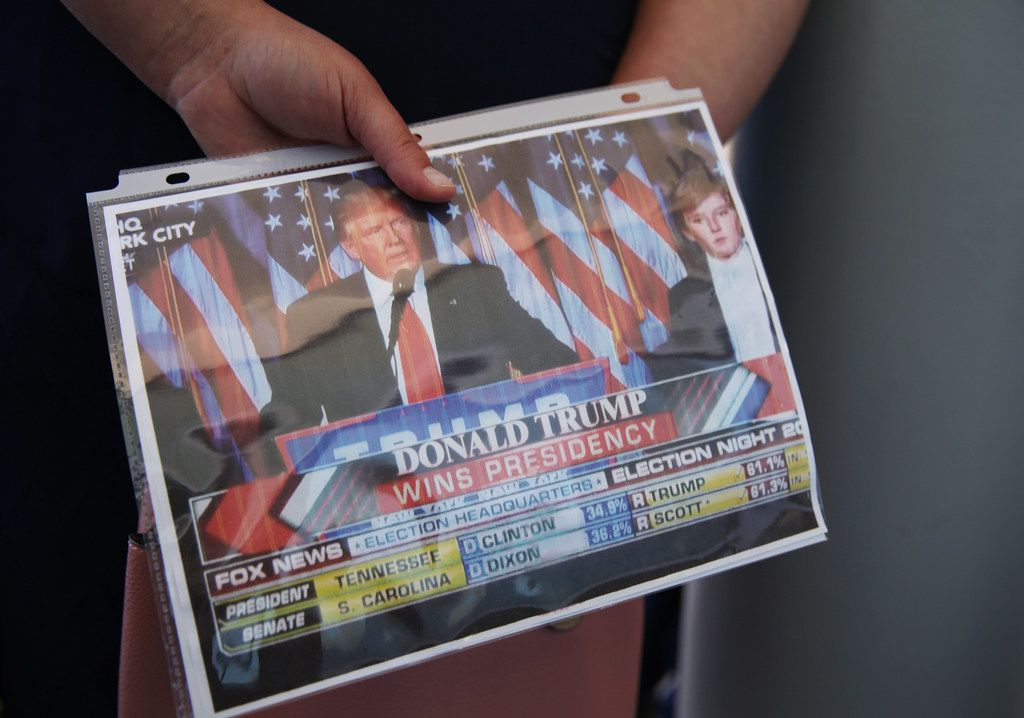A supporters of President Donald Trump holds onto a printout of the President from election night while waiting for the arrival of Trump before a visit to Dallas while at Dalfort Fueling near Love Field in Dallas Wednesday October 25, 2017. President Trump will participate in a hurricane recovery briefing, a Republican National Committee roundtable and give remarks at a reception. (Andy Jacobsohn/The Dallas Morning News)