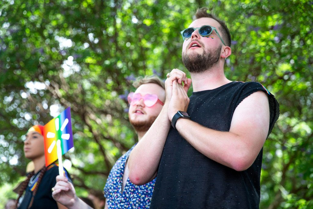 Alex Karshis, right, of Houston, watches the parade go by along with Sean Christopher, center, during the annual Dallas Pride / Alan Ross Texas Freedom Parade at Fair Park in Dallas on Sunday, June 2, 2019. (Shaban Athuman/Staff Photographer)