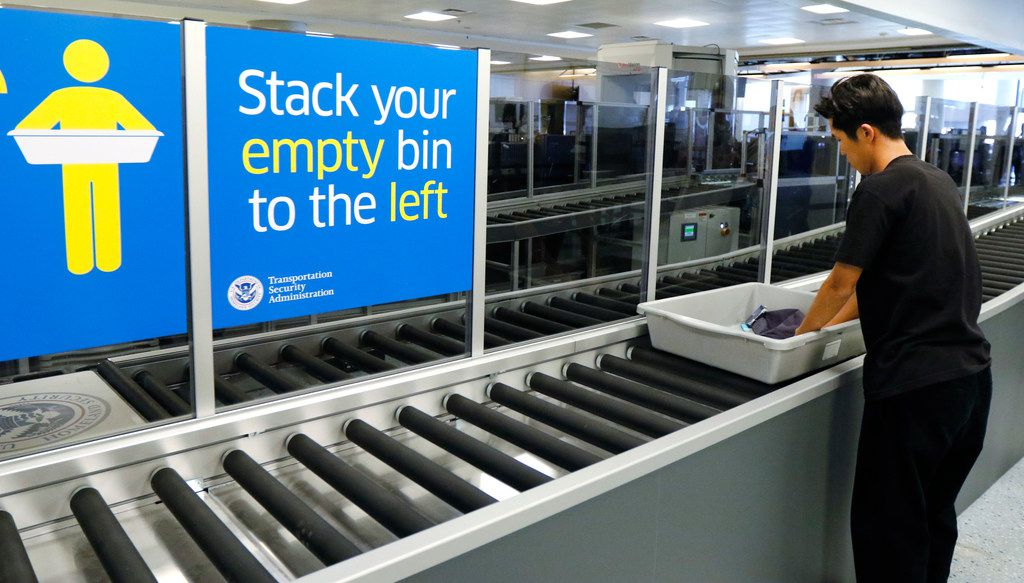 Takahshi Ryosuke of Japan takes his personal belongings from a bin after using an automated lane at Dallas/Fort Worth International Airport on Thursday, October 12, 2017.