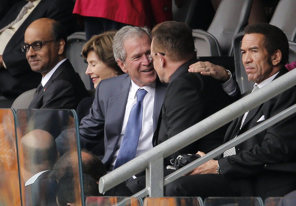 Former U.S. President George W. Bush, left, embraces Irish rock star Bono during the memorial service for former South African president Nelson Mandela at the FNB Stadium in Soweto, near Johannesburg, South Africa, Tuesday Dec. 10, 2013. (AP Photo/Peter Dejong)