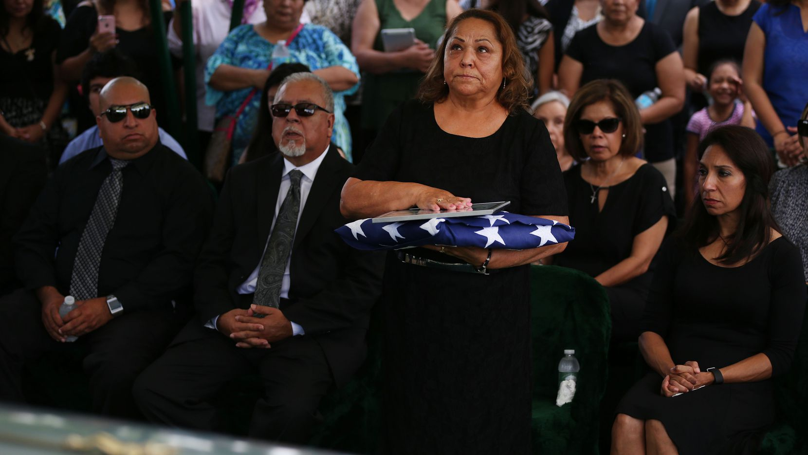 Maria Ramirez, wife of Felix Lozada, stands after military funeral honors during Lozada's burial service at Calvary Hill Cemetery in Dallas on Saturday.