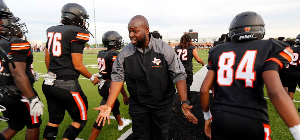 Lancaster head coach Christopher Gilbert slpas hands with his players after the team's introduction at Beverly D. Humphrey Tiger Stadium in Lancaster Texas, Friday, August 30, 2019. Lancaster was facing Duncanville in the season opening game. (Tom Fox/The Dallas Morning News)