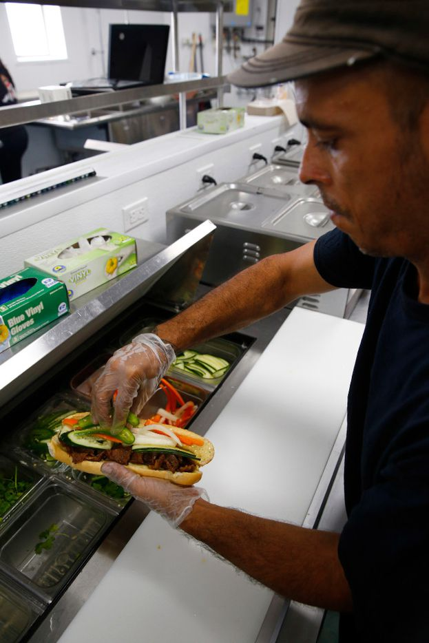A lemongrass chicken banh mi sandwich is assembled by Carlos Cresto at Sandwich Hag in Dallas on July 7, 2017.  (Nathan Hunsinger/The Dallas Morning News)
