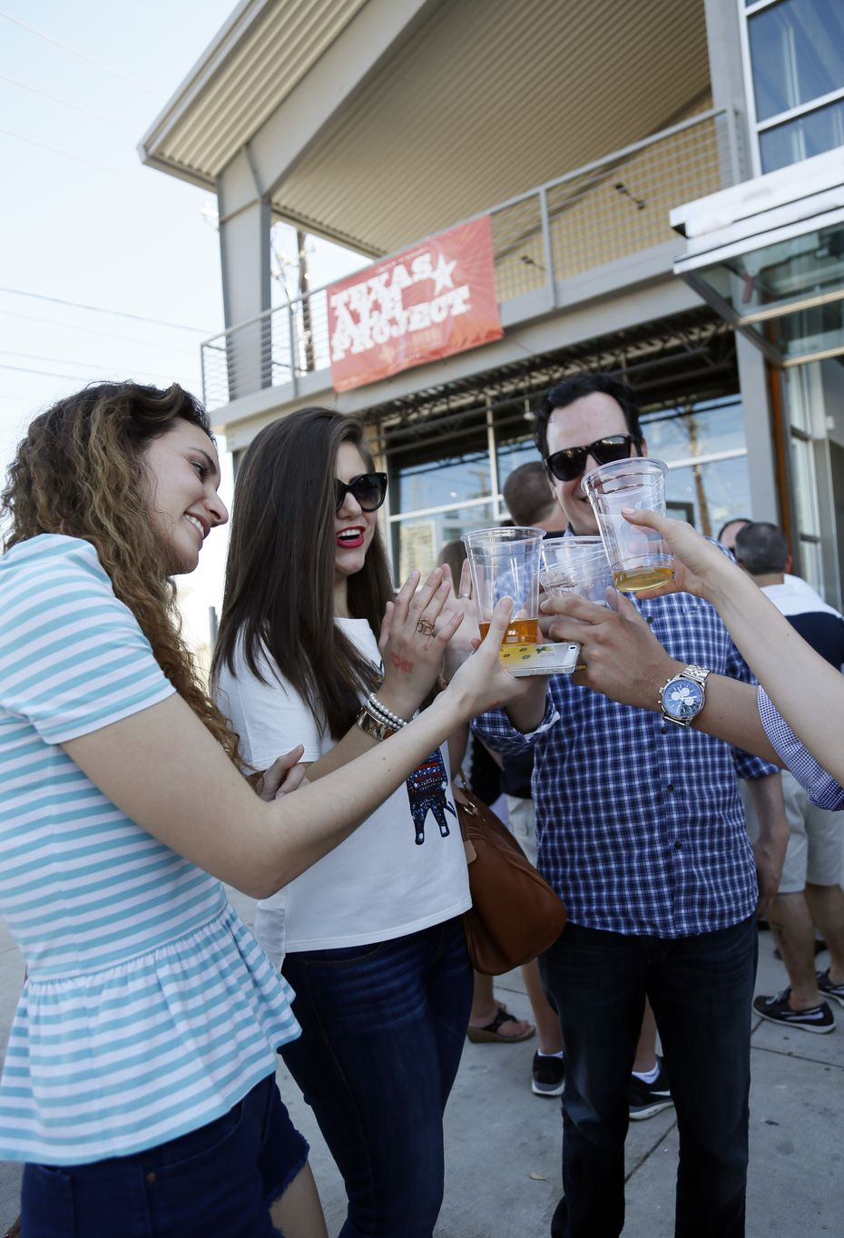 Elia Torres, Hileana Tamez, Jorge Muza and other friends (not shown) cheers at Texas Ale Project's grand opening April 25, 2015.