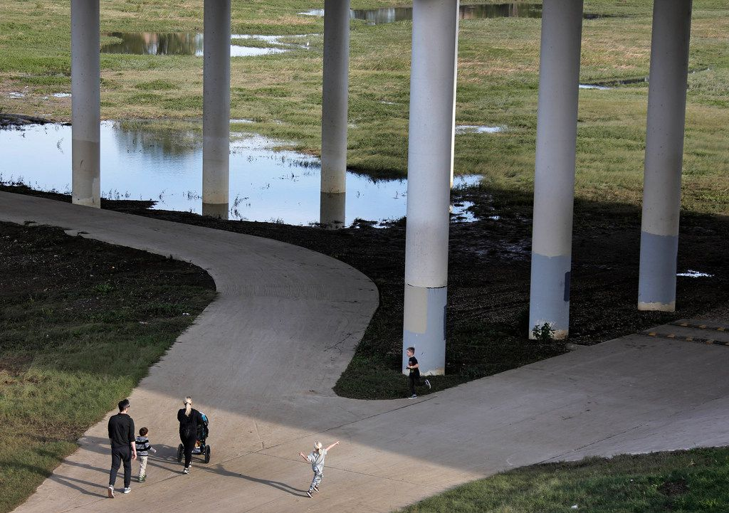 A family walks along a paved path in the Trinity River basin off of Canada Drive in West Dallas, part of the bicycle trail project that has been fully funded but not yet completed, photographed on Tuesday. (Louis DeLuca/The Dallas Morning News)