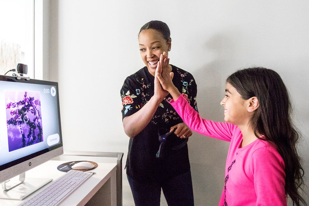 Courtney Johnson, process manager at Capital One, high-fives Carmen Sanchez, 9, of Dallas after seeing the results of Carmen's Braintone Art session.