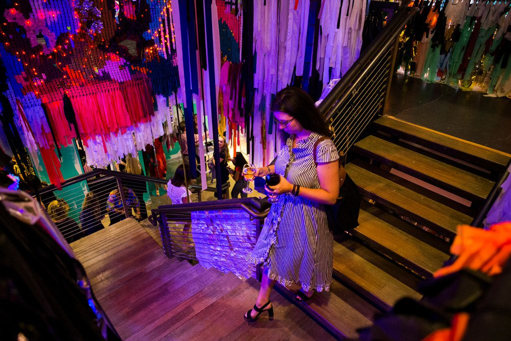 A woman walks down a staircase adorned with artwork by The Color Condition. Psychedelic Robot is a two-story, 12,000-square-foot art wonderland.
