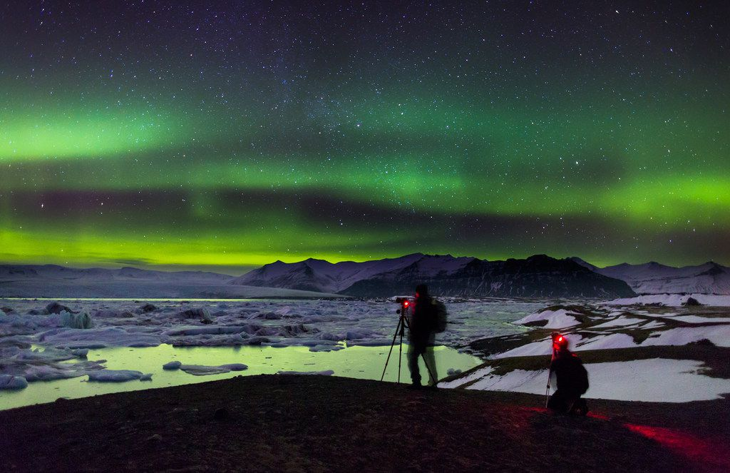 Photographers try to capture the brilliant color of the northern lights at the Jökulsárlón glacial lagoon in southeastern Iceland.