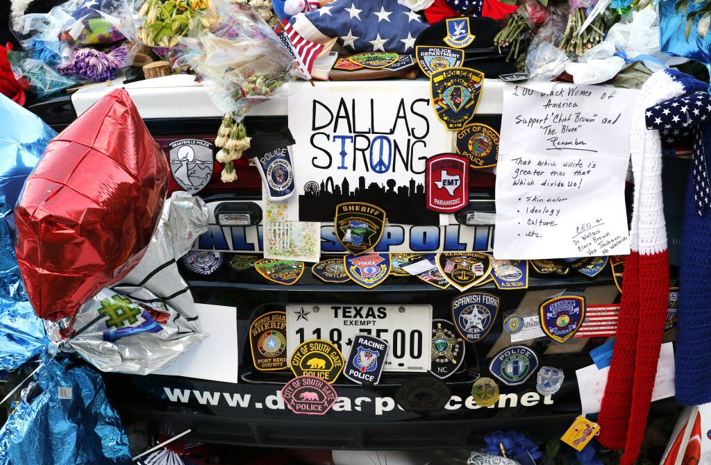 Two Dallas police cars are covered with notes, flowers, balloons and other items as part of a makeshift memorial at the Jack Evans Police Headquarters.
