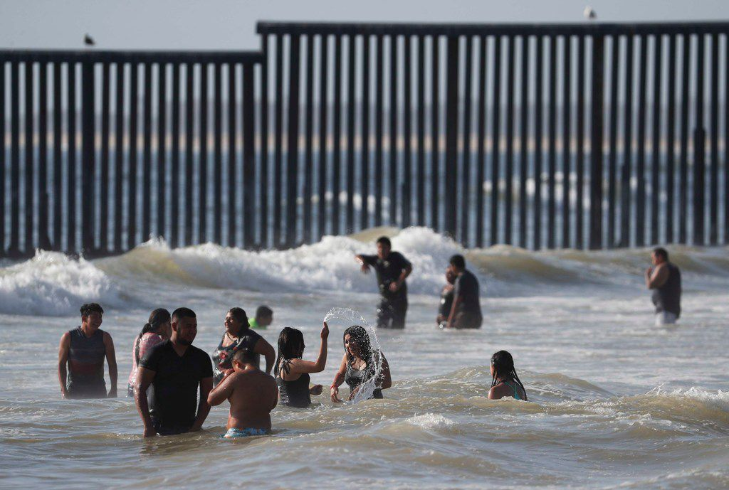 People enjoy the beach near the U.S. border wall in Tijuana, Mexico, Sunday, June 9, 2019.