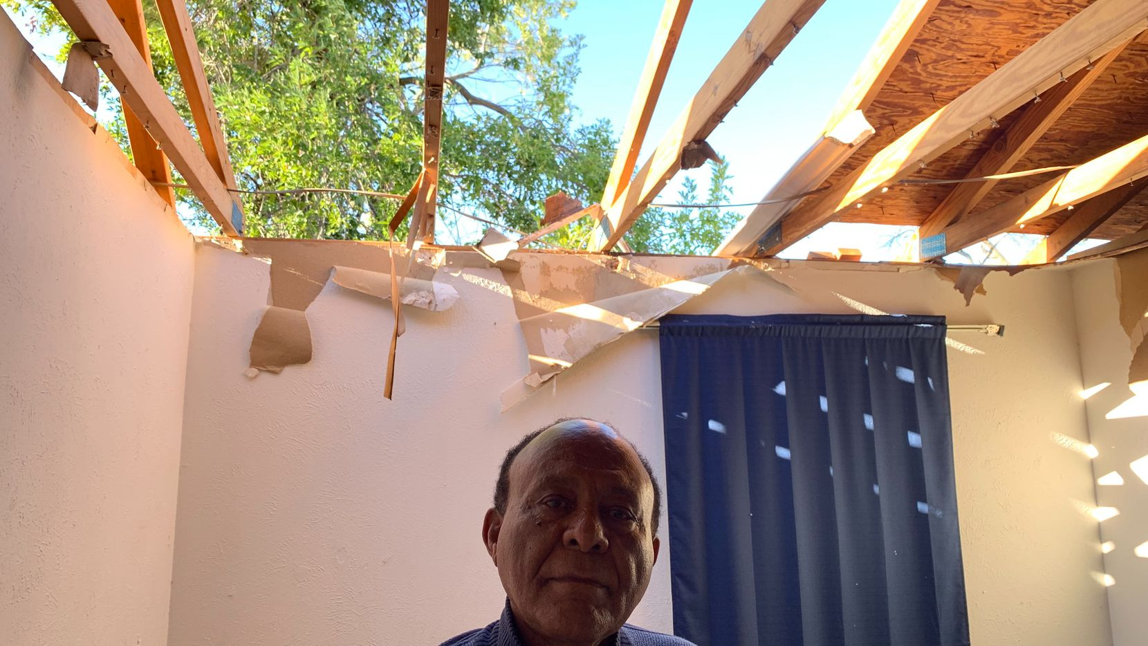 Gizaw Gedlu, 71, stands in his Richardson home that was destroyed by a tornado Sunday night.