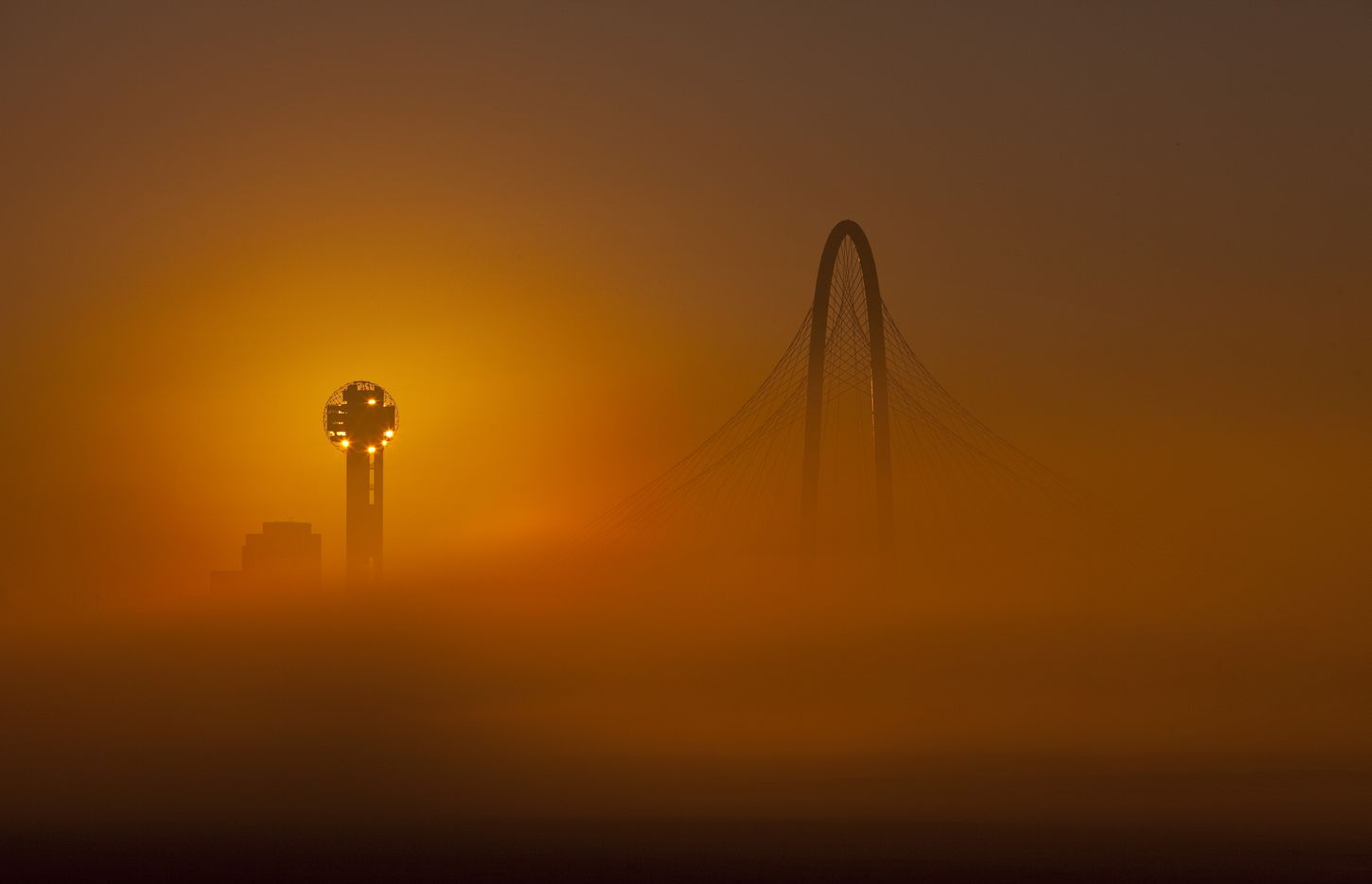 Spanning the Trinity River between downtown and West Dallas, the 400 ft. high Margaret Hunt Hill Bridge is seen through the fog with the rising sun behind Reunion Tower, January 11, 2012. (Tom Fox/The Dallas Morning News)