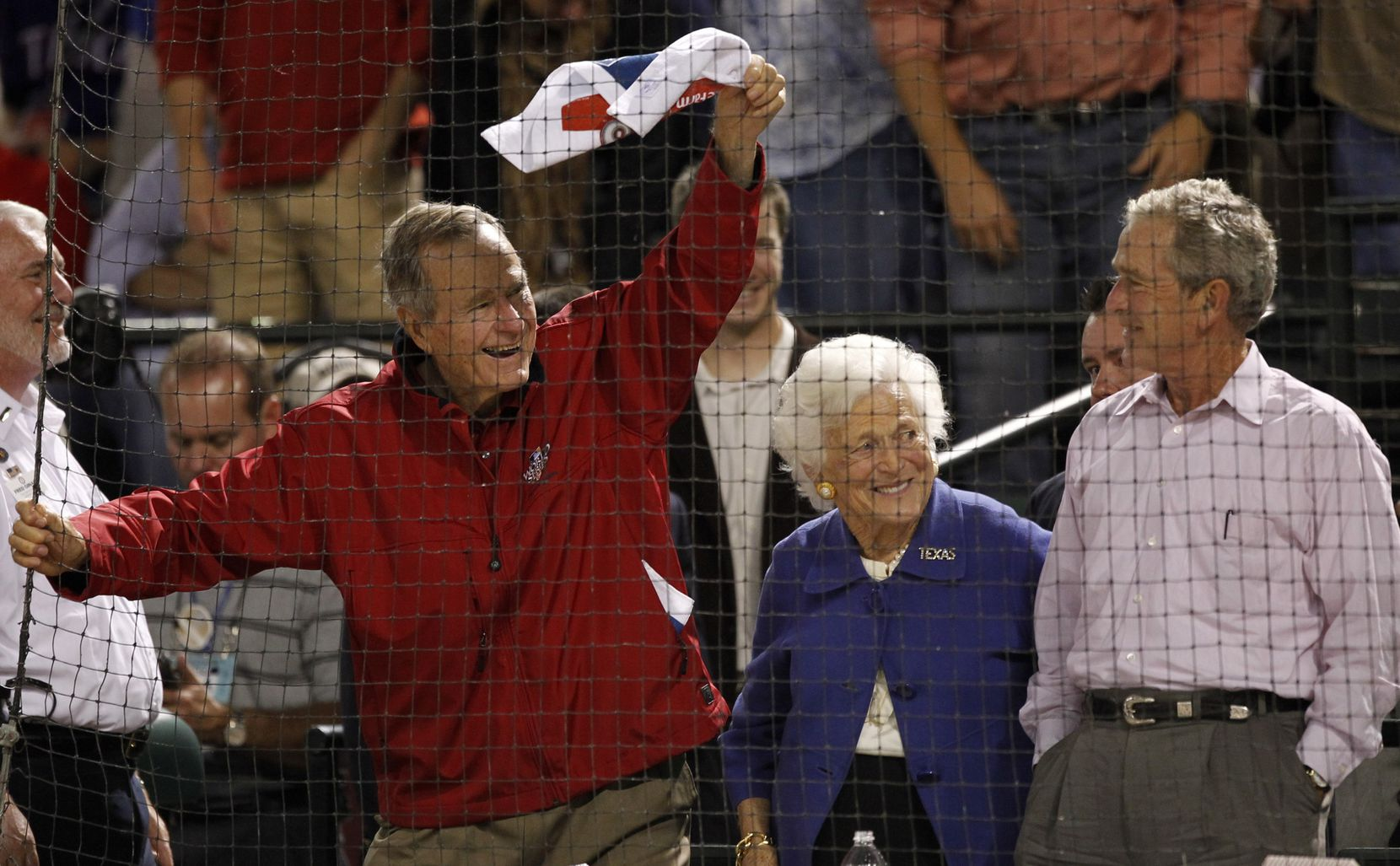 Former president George H.W. Bush waves a towel as wife Barbara and son George W. Bush look on during the World Series Game 4 between the Texas Rangers and San Francisco Giants at Rangers Ballpark in Arlington on Oct. 31, 2010.