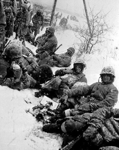 U.S. Marines, fighting their way from Chosin to Hungnam, Korea, take a rest in the snow somewhere on the route in December 1950 during the Korean War.