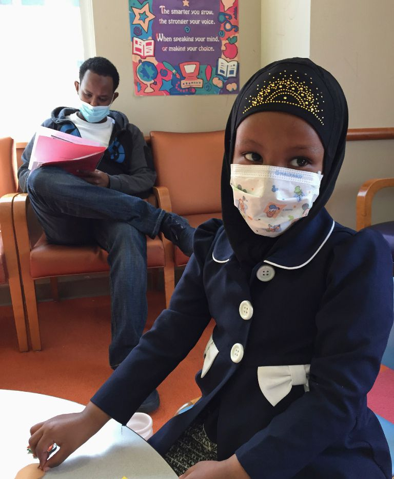 Amira Hassan of Burnsville, Minn., plays in the waiting room at a clinic in Minneapolis. She and her father have to wear masks to protect themselves from measles after a recent outbreak sickened children.
