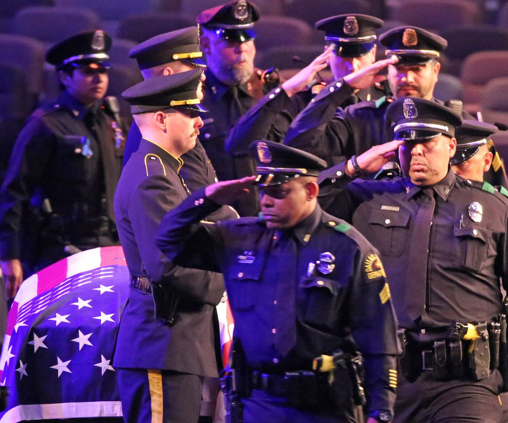 Dallas police officers salute their fallen comrade during the uniformed officers pass-by at the funeral for Officer Rogelio Santander.