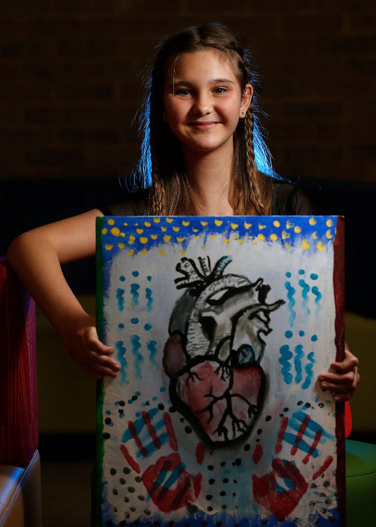 At a follow-up visit to scoliosis surgery, Alexis Brown poses at Texas Scottish Rite Hospital for Children with her painting of a heart.