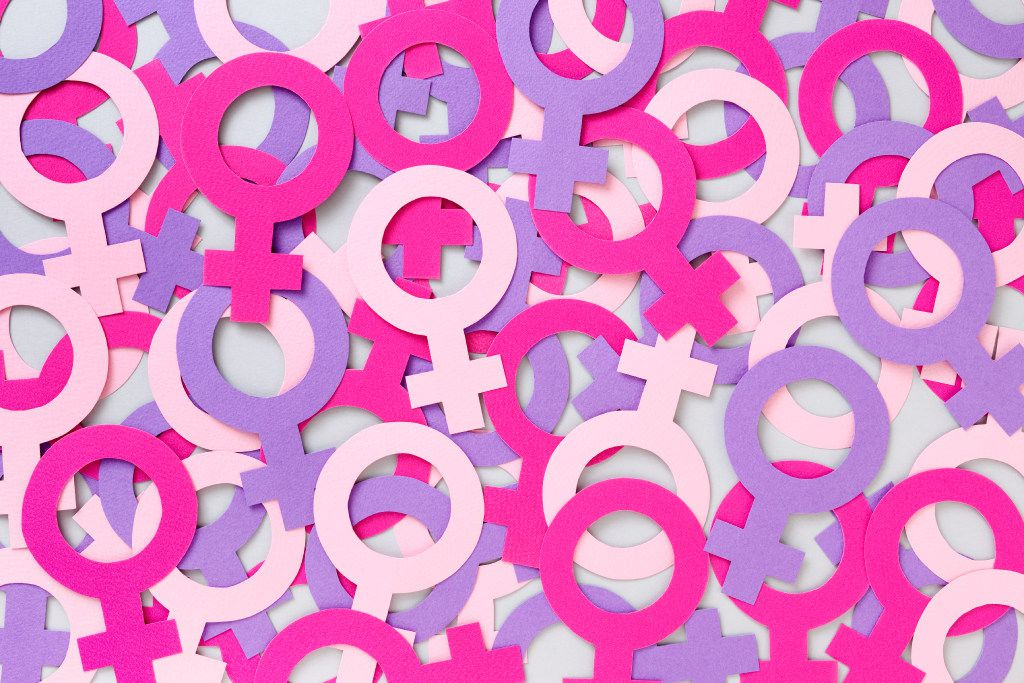 Illustration showing a collection of women's symbols. Lots of paper cutouts of male symbols in shades of pink creating a background