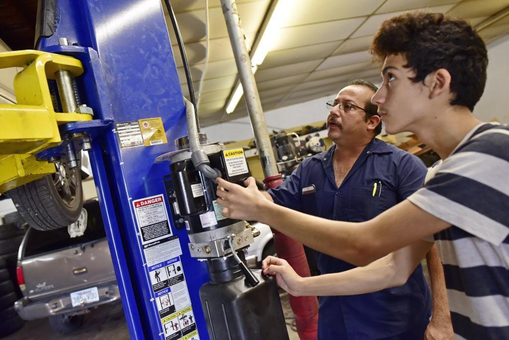 Joaquín Godínez (izq.) y su hijo Cristian, de 14 años, trabajan en su taller mecánico de Pleasant Grove.  BEN TORRES/AL DIA