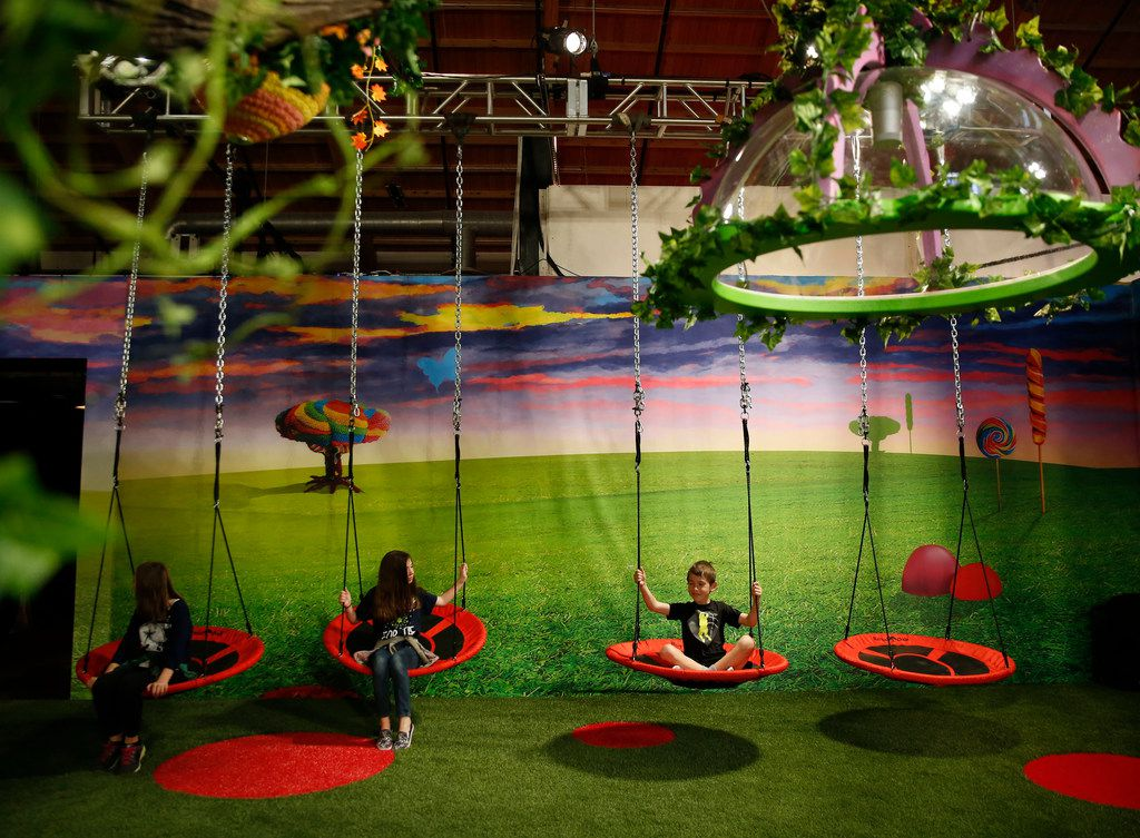 Siblings (from left) Abigail Corder, 11, Allison Corder, 11, and Peyton Corder, 8, swing in Candytopia, an immersive pop-up art exhibit, in Dallas on Thursday, April 4, 2019.  (Rose Baca/Staff Photographer)