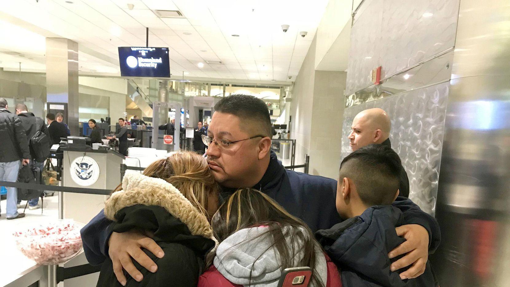 Jorge García abraza a su esposa Cindy garcía y sus dos hijos en el Detroit Metro Airport antes de abordar un vuelo a México.(AP)
