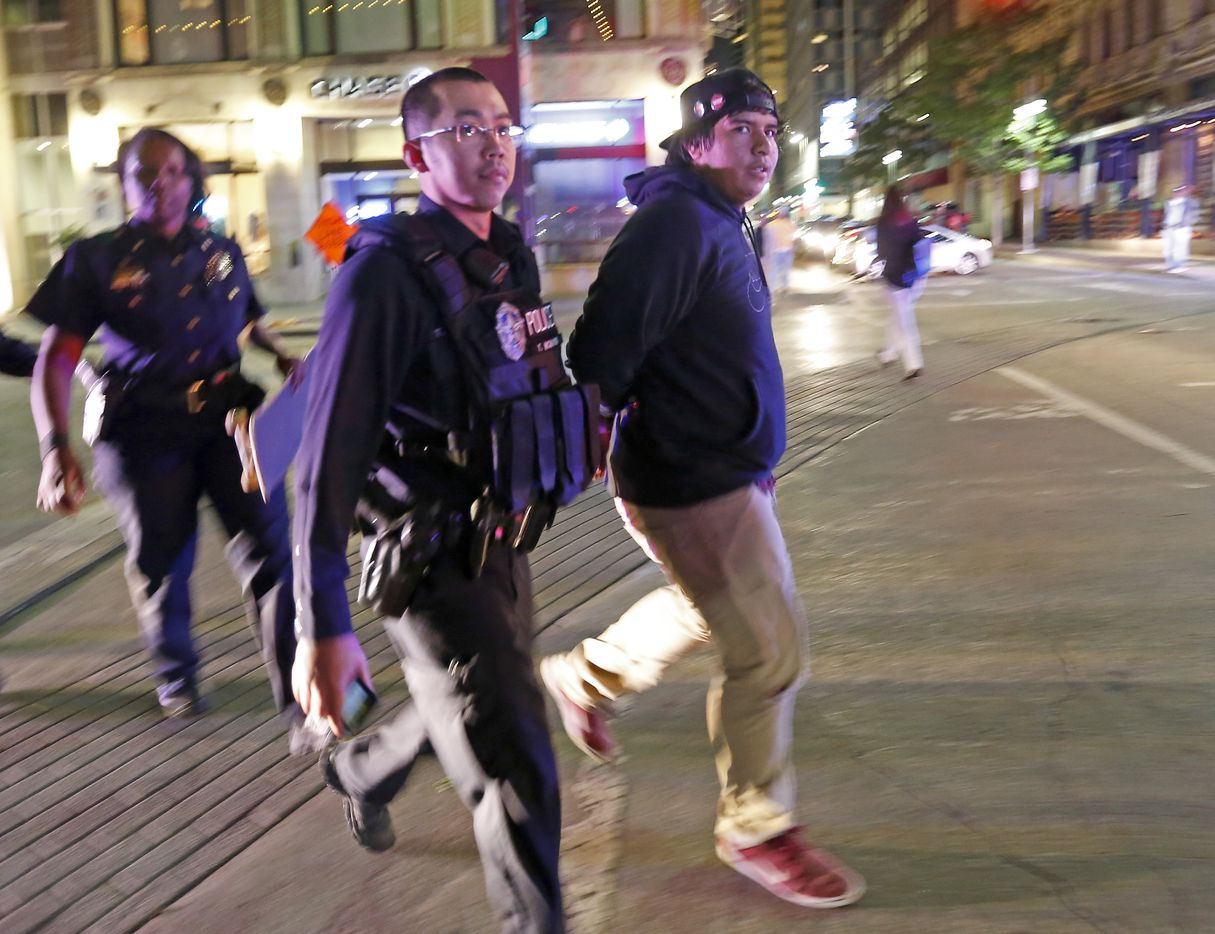 A protester against President-elect Donald Trump is detained while marching in downtown Dallas, Thursday, Nov. 10, 2016.