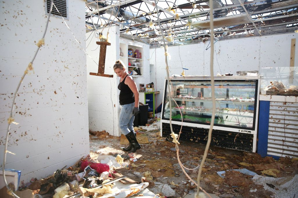 Melissa Smith, owner of the Always Sunny Fudge and Ice Cream in Rockport, walks through her shop while cleaning up storm damage on Wednesday.