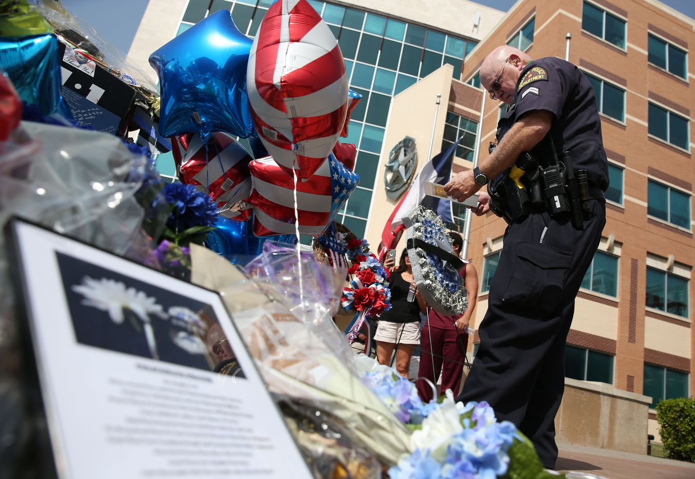 Dallas police officer Jon Lumbley reads a card that was left  at the memorial for fallen officers at Dallas Police headquarters in Dallas on Saturday, July 16, 2016.