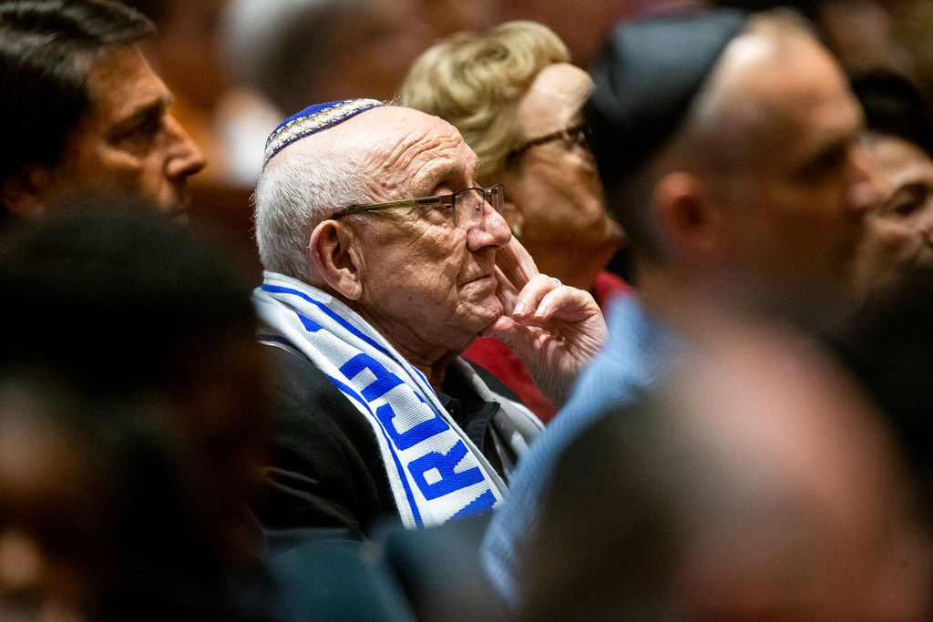 Holocaust survivor Max Glauben listens as Bradley Laye, president and CEO at the Jewish Federation of Greater Dallas, gives remarks during a community service of hope and healing at Congregation Shearith Israel in Dallas on Oct. 28, 2018