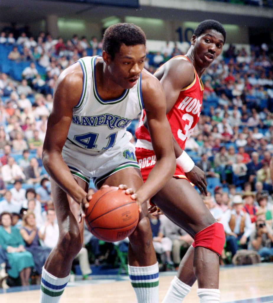 Dallas Mavericks' Sam Perkins and Houston Rockets' Akeem Olajuwon in action during the first half of a game at Reunion Arena.