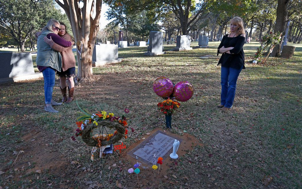Laura Heinemann, a friend of Taylor Gruwell, hugs Norris at Gruwell's grave at Greenwood Memorial Park in Fort Worth on Wednesday. On the right is Angela's friend Peggy MacKenzie.