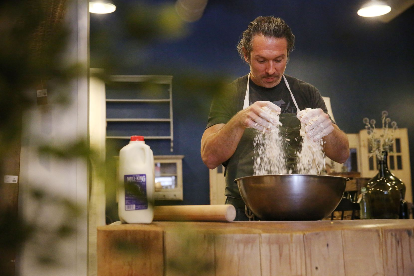 Chef Robert Lyford combines ingredients while preparing cheddar biscuits at Patina Green Home and Market in McKinney.