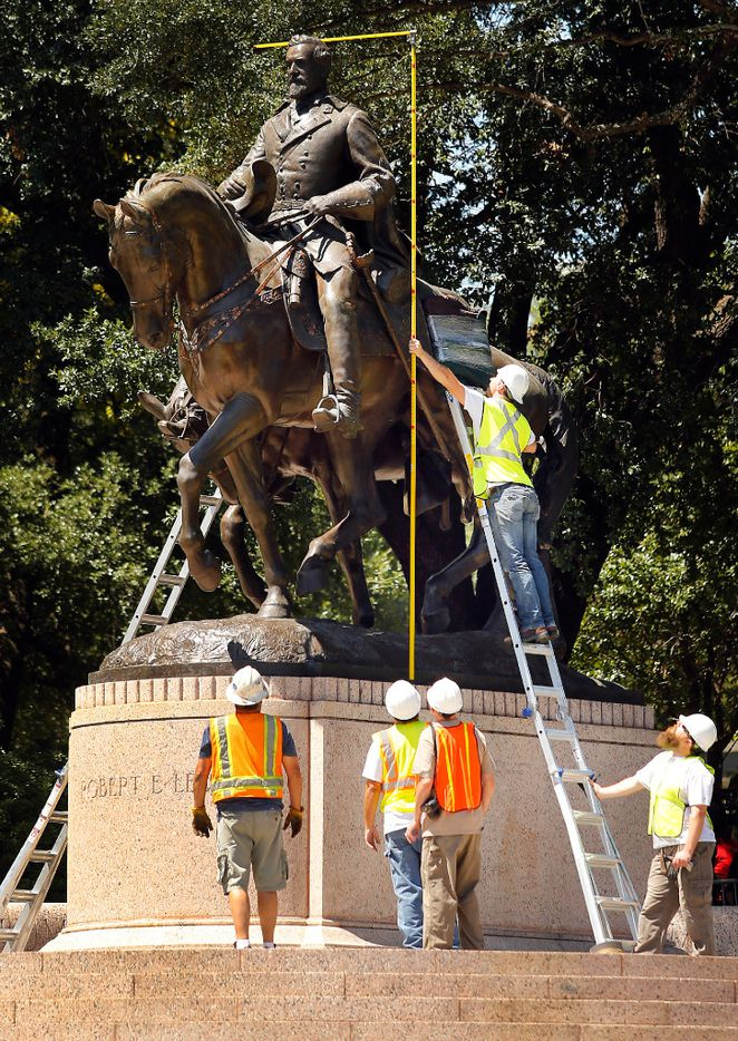 Crewman from Howell Crane and Rigging Inc. measure the height of the Robert E. Lee statue before trying to remove it from Robert E. Lee Park in Dallas on Sept. 6. Earlier in the day the Dallas City Council voted 13-1 for immediate removal of the monument to the Confederate general with a soldier at his side. The removal was halted though by a temporary restraining order from U.S. District Judge Sidney A. Fitzwater.