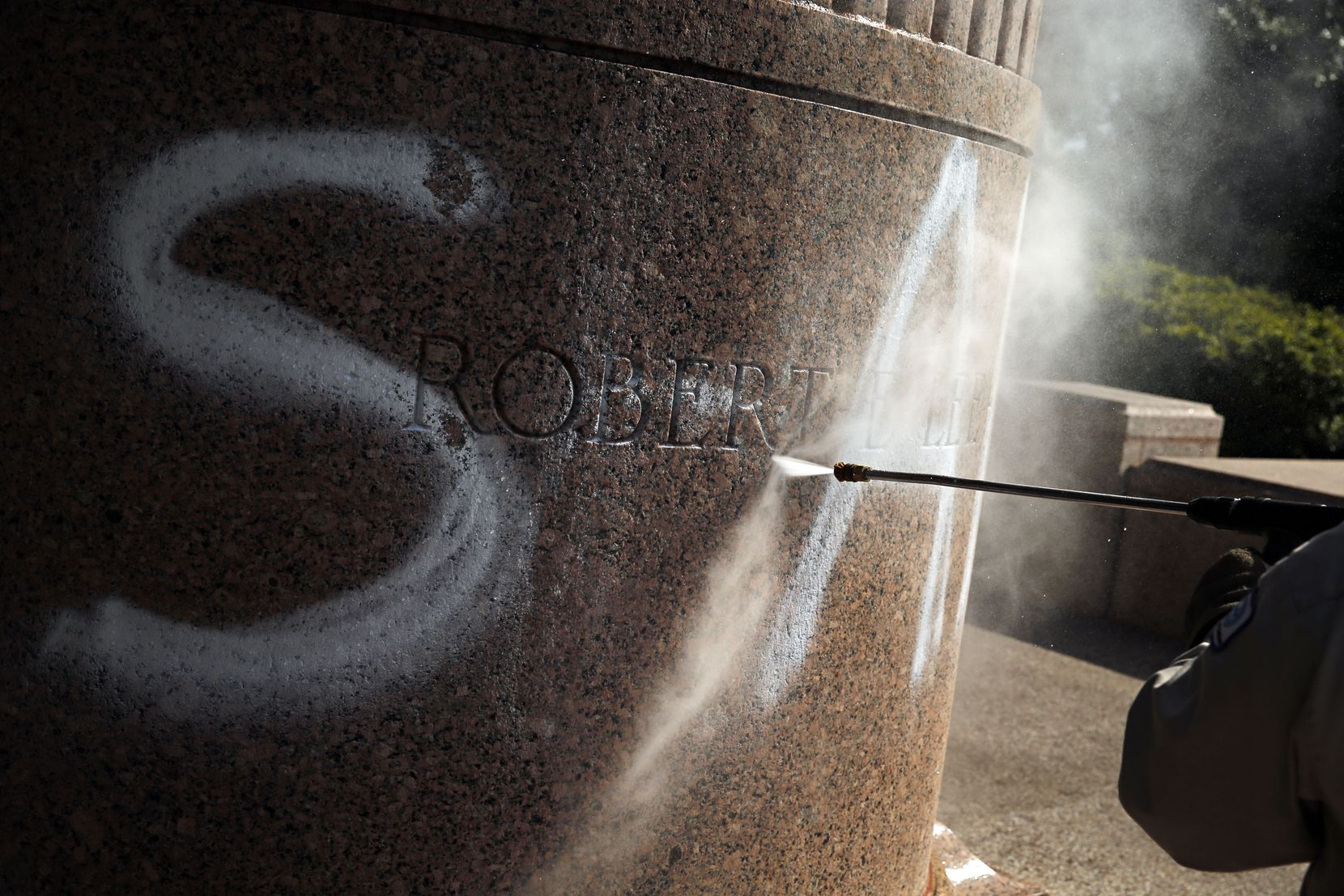 """Tino Banda, an employee of the City of Dallas Parks and Recreation Department, uses a power washer to remove the spray-painted word """"SHAME"""" from a statue of General Robert E. Lee at Robert E. Lee Park on July 10, 2015."""