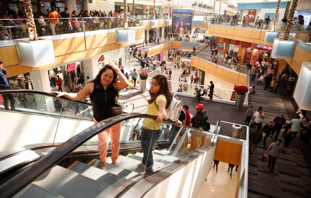 Blanca Spreen and her daughter Grace ride up the escalators at Galleria Dallas.