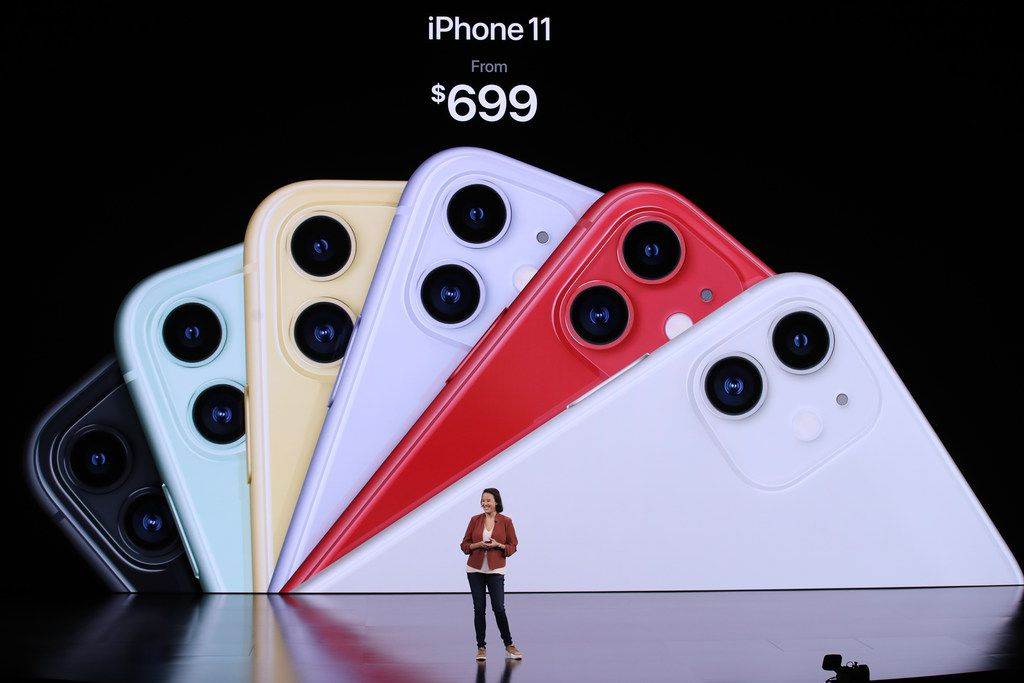 The iPhone's new color scheme is projected behind Drance.