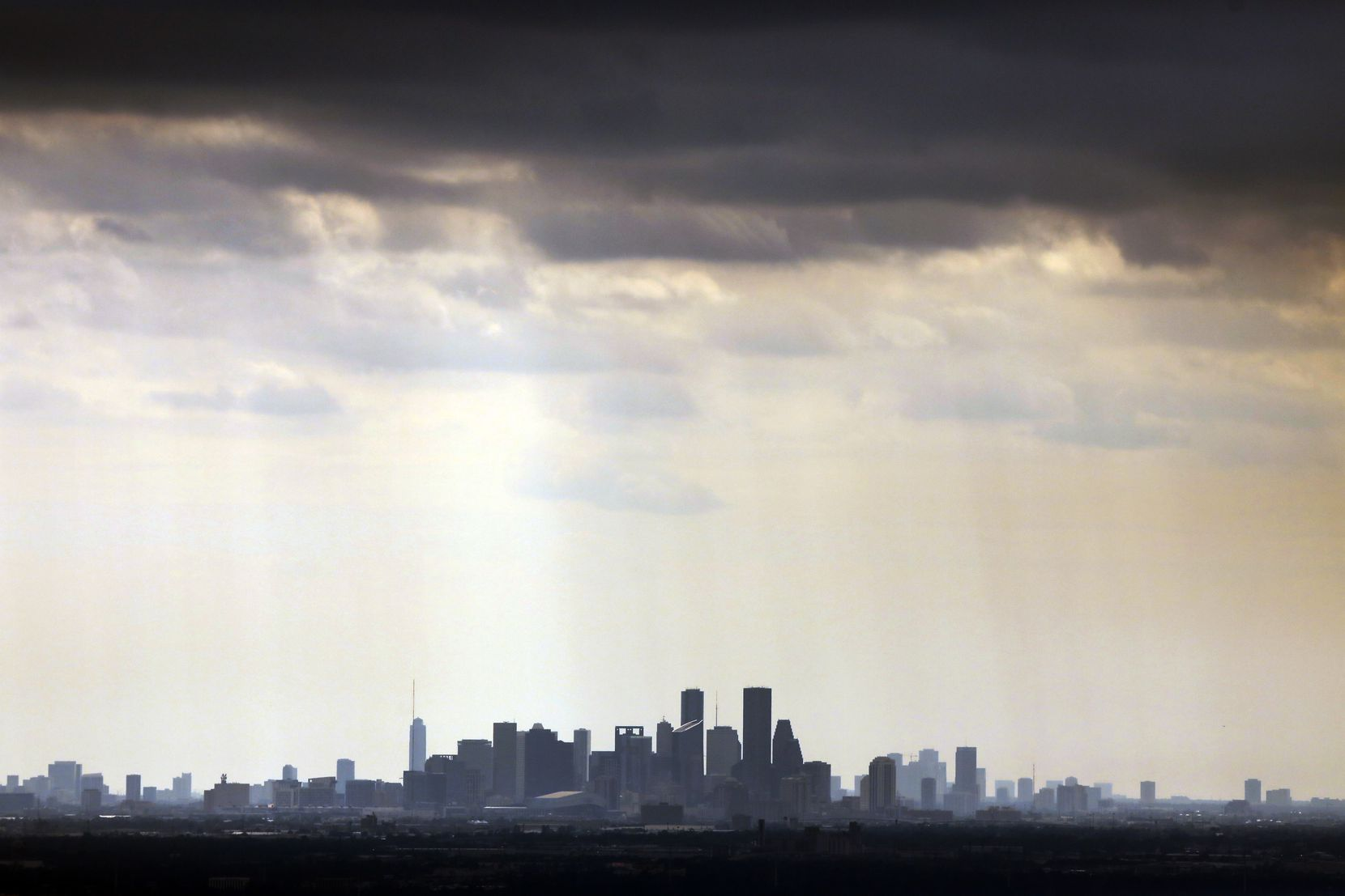 Lingering light rain falls near downtown the Houston, Texas skyline, Wednesday afternoon, August 30, 2017.
