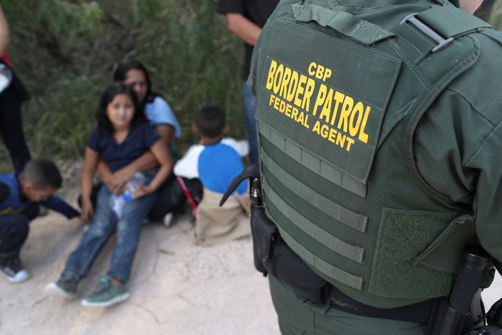 Central American asylum seekers wait as U.S. Border Patrol agents take them into custody on June 12 near McAllen, Texas. The families were then sent to a U.S. Customs and Border Protection (CBP) processing center for possible separation.