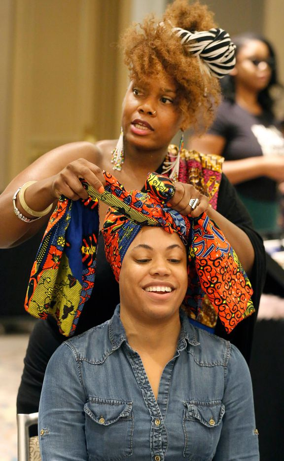 Iyabo Spears-Borokini, standing, ties a head wrap for Ashley Frye during the Afrolicious Hair and Beauty Expo at the Dallas Westin Park Central in north Dallas on Sunday, August 5, 2018.