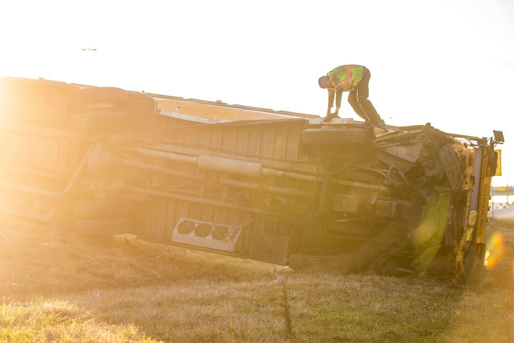 A worker stands on top of a school bus from Bishop Dunne Catholic School that overturned in the westbound lanes of I-30 near Loop 12 in Dallas on Thursday, Jan. 17, 2019. Multiple people onboard the bus were been taken to nearby hospitals after the crash.