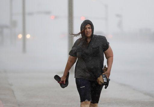 Hillary Lebeb camina por un rompeolas en Galveston, Texas, mientras el huracán Harvey cobra fuerza en el Golfo de México, el viernes 25 de agosto del 2017. El Centro Nacional de Huracanes prácticamente se está quedando sin palabras alarmantes para describir al huracán Harvey e instar a la gente que se alejen de su ruta. (AP Foto/David J. Phillip)