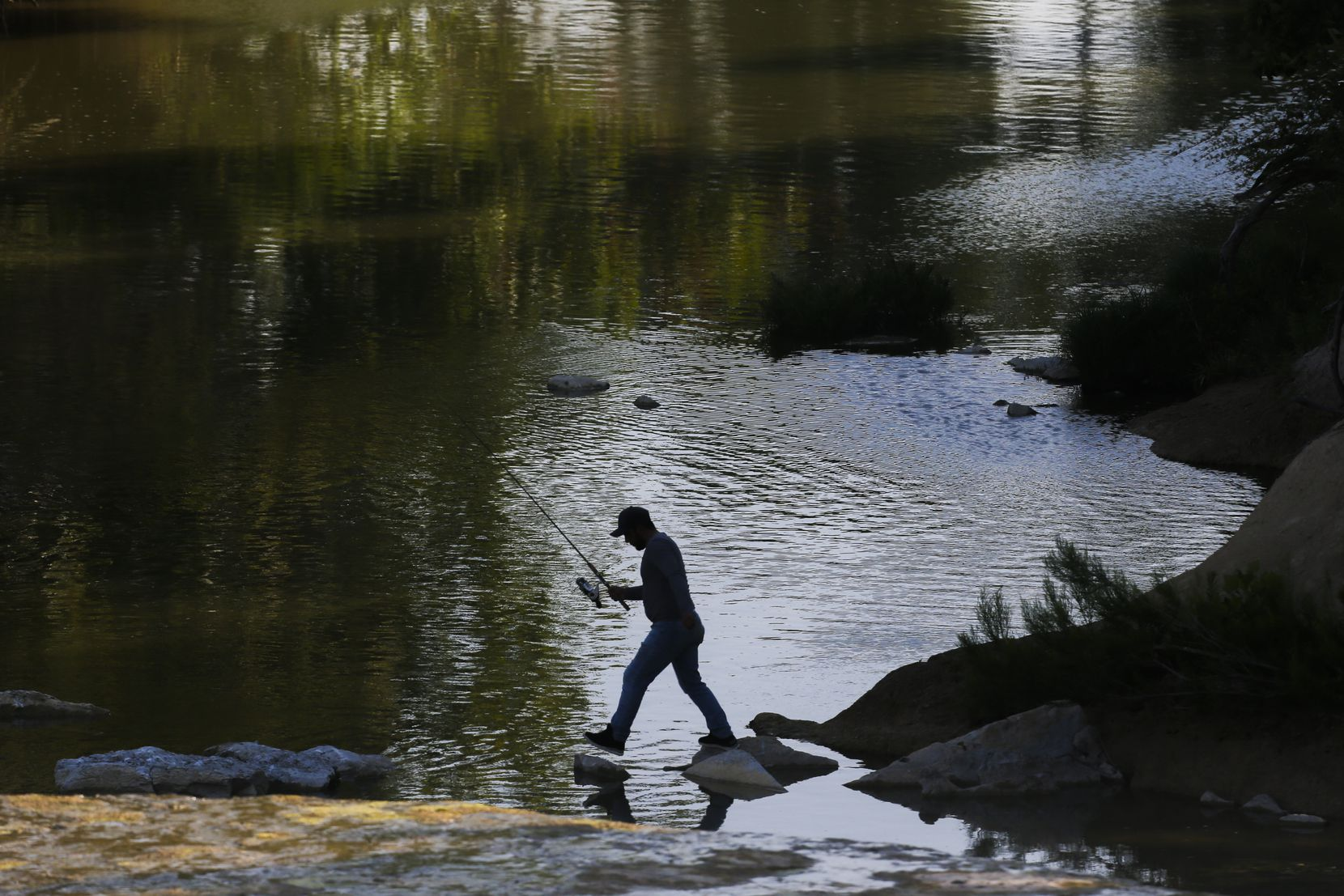 A fisherman hops from rock to rock down creek from where officials surveyed the spillway at White Rock Lake on July 25, 2019, in Dallas.