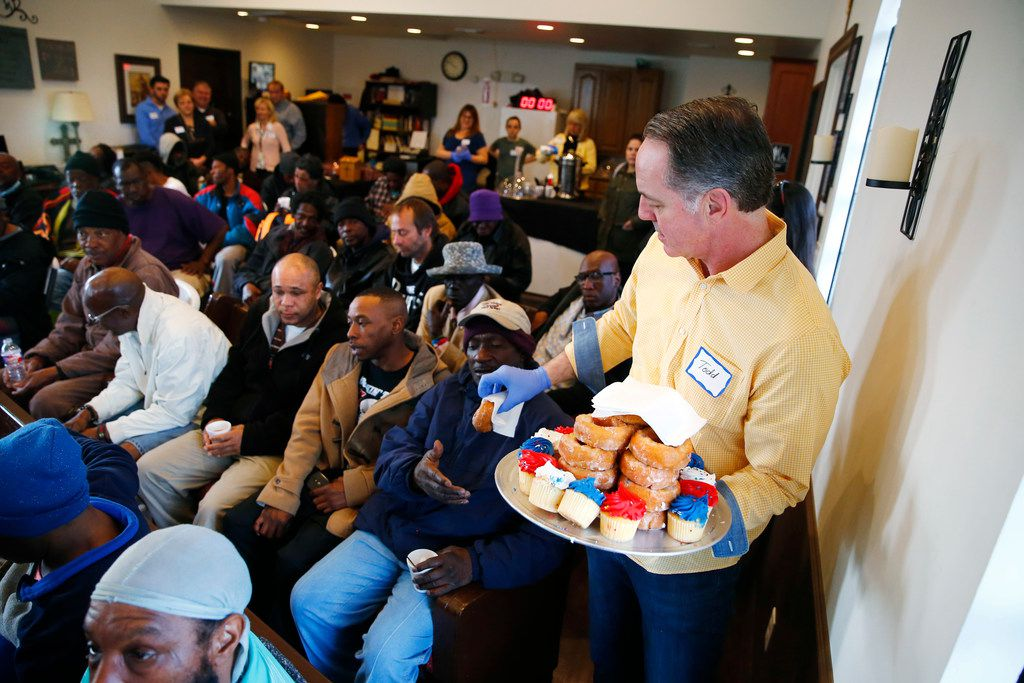 Todd Garner hands out pastries before worship service at SoupMobile Church for the homeless in Dallas on Feb. 4, 2018.