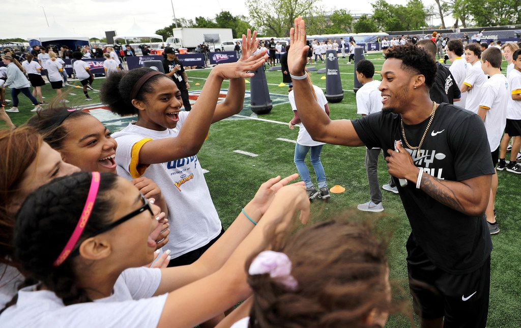 NFL Draft prospect Ohio State's Denzel Ward, right, gives high-fives to participants during a Play Football Clinic Wednesday, April 25, 2018, in Arlington, Texas. The 2018 NFL Draft begins Thursday, April 26, 2018, at AT&T Stadium. (AP Photo/David J. Phillip)