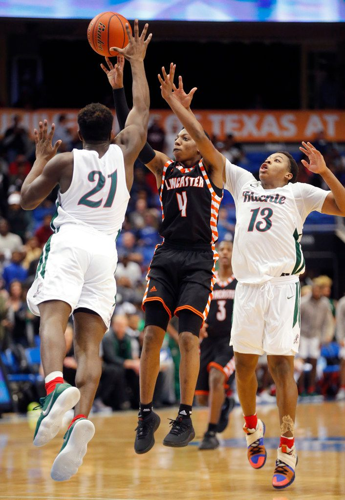 Lancaster Wade Taylor (4) attempts a three-point shot as Waxahachie junior guard Demani Richardson (21) and senior guard Mar'Qualen Grant (13) defend during the second half of a Class 5A Region II quarterfinal boys basketball game at UT-Arlington, Tuesday, February 27, 2018. Lancaster won 75-67. (Brandon Wade/Special Contributor)
