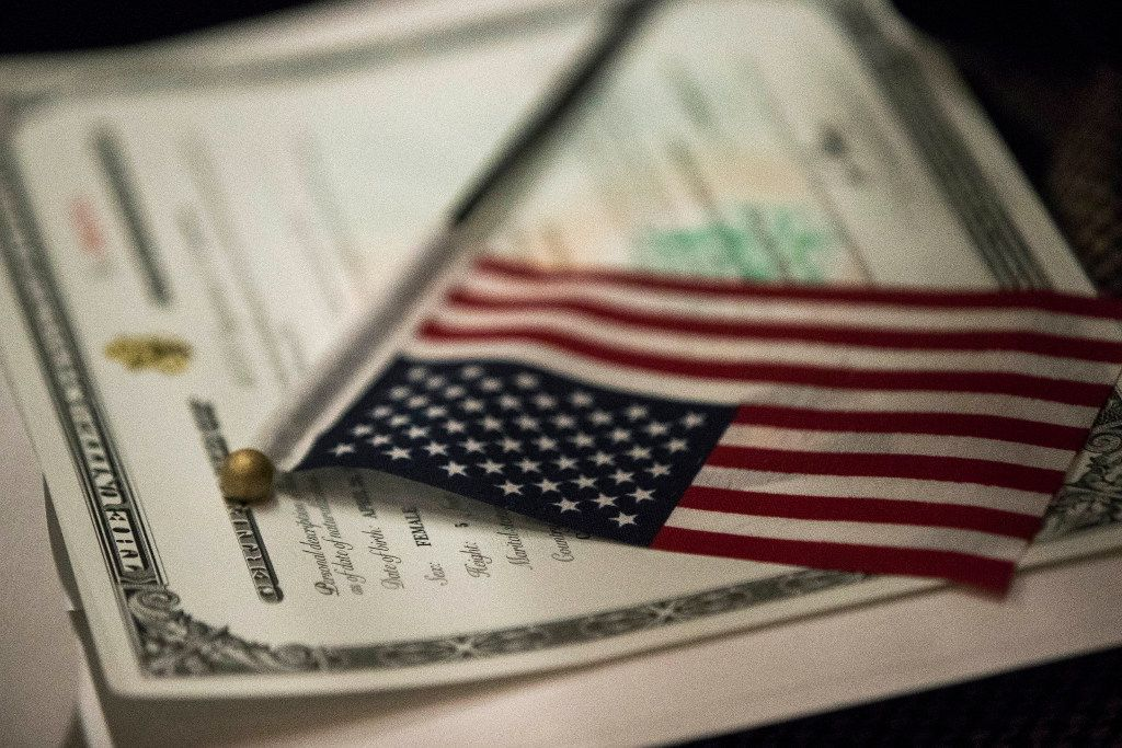 An American flag rests on a certificate of citizenship during a naturalization ceremony in New York. (Mary Altaffer/The Associated Press)